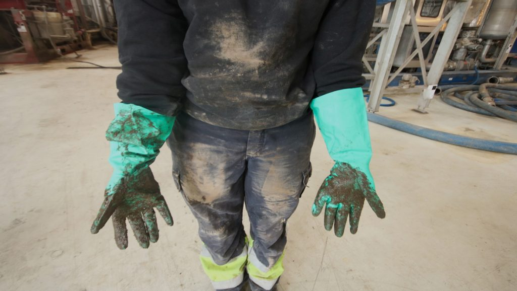 Bilde av person med hansker og iført olje.