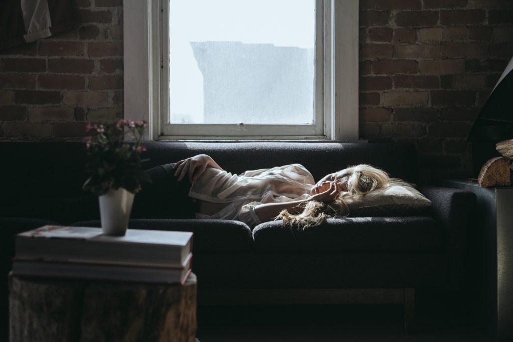 Bilde av dame som ligger på sofa og ser trøtt ut.