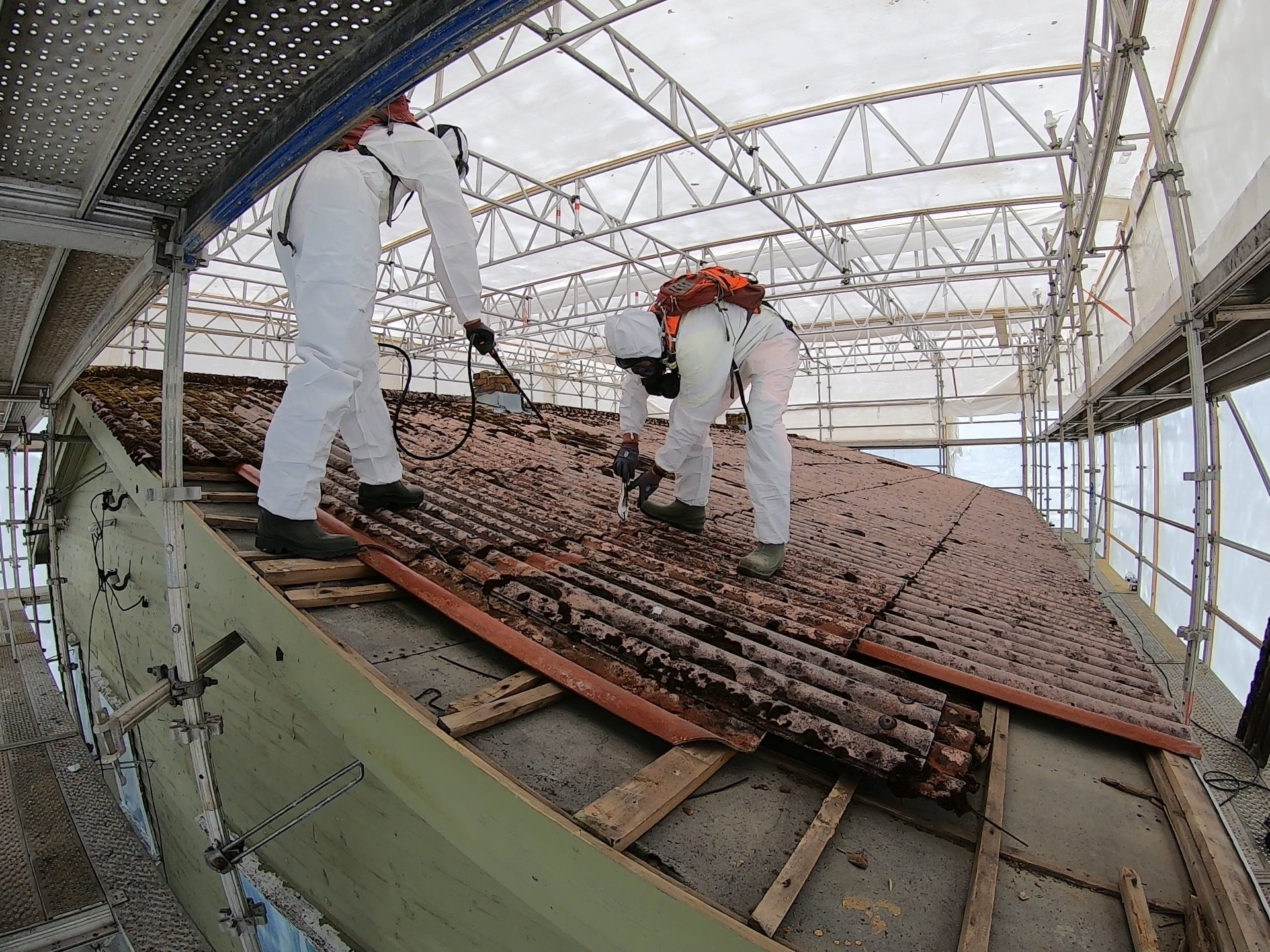 To menn i hvite vernedrakter og vernemasker arbeider med sanering av taket på et bygg.