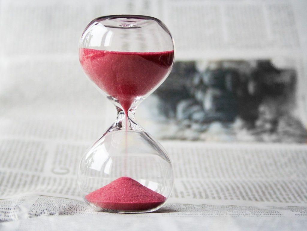 Bilde av et timeglass med rød sand