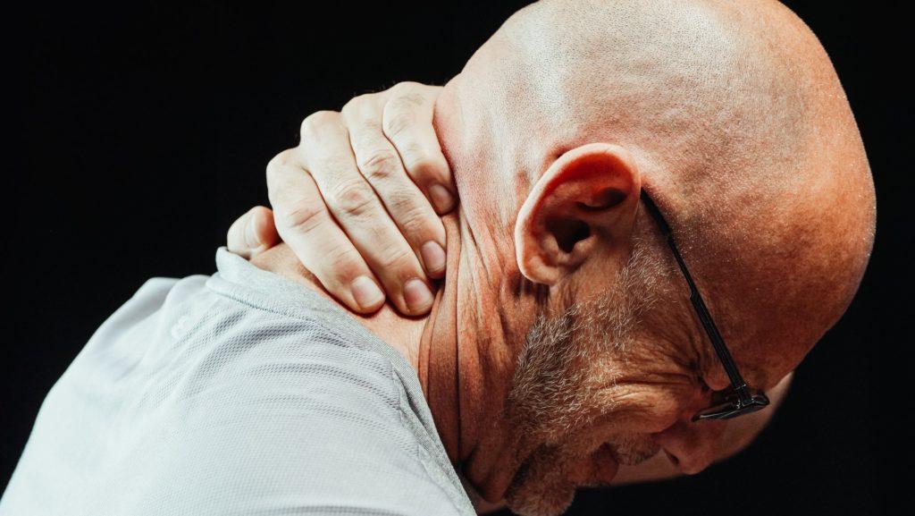 Mann tar seg om nakken i smerter.