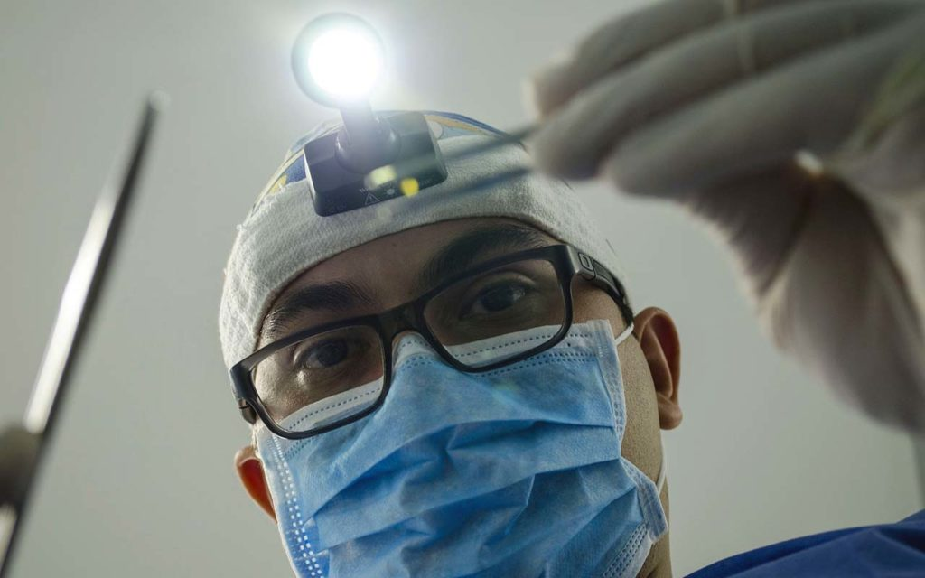 Tannlege med munnbind klart til å undersøke en pasient.